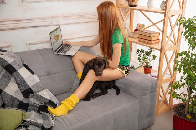 Home portrait of cute girl hugging with puppyon the sofa, using modern devices, gadgets and having fun. pet's love, youth culture, home comfort and remote education concept.