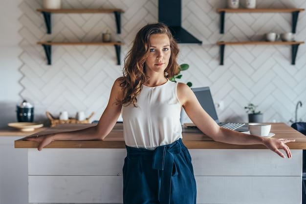 テーブルに立っている美しい若い成功した女性の家の肖像画。