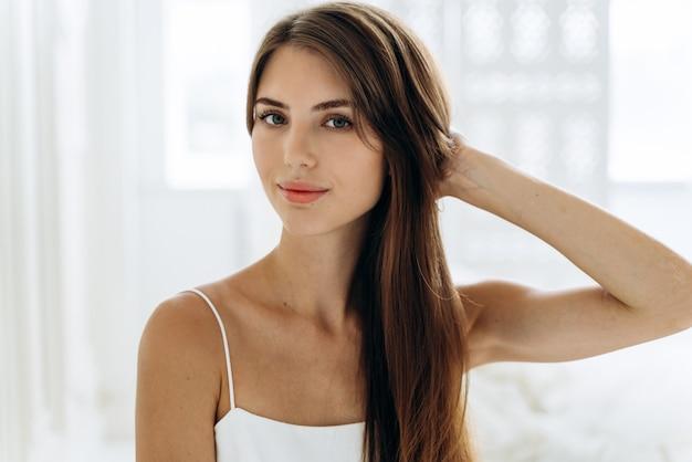 그녀의 아파트에서 아침을 보내는 동안 차분한 표정으로 카메라 앞에 앉아 건강한 피부를 가진 사랑스러운 갈색 머리 여성의 가정 초상화. 아름다움과 여자 외모 개념