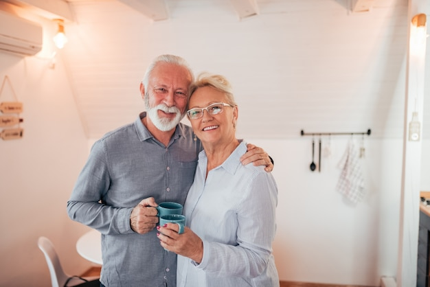 Home portrait of a senior couple holding mugs, looking at camera.