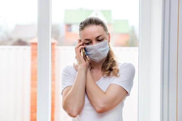 自宅検疫。病気の休暇中に医療用防護マスクで白人女性が電話をかけ、救急車を呼ぶ。