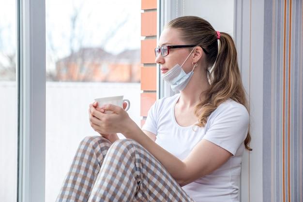 自宅検疫。病気休暇の白人女性は、薬用ハーブティーまたは水を飲んで、医療用防護マスクの窓に座っています。
