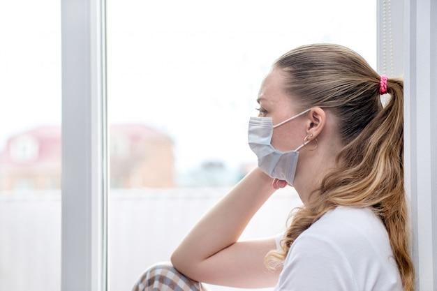 自宅検疫。病気の休暇の白人女性は医療用マスクのウィンドウに座っています。体調不良、インフルエンザウイルスと風邪の流行。
