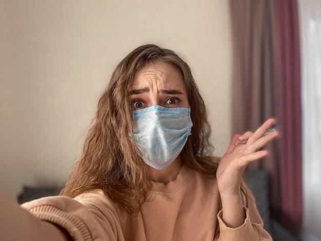 家庭検疫コンセプト、若い女性は自宅で防護マスクを着用しています。 covid-19の予防