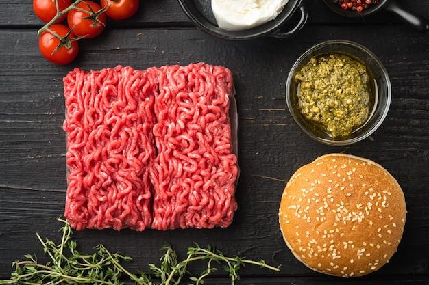 Домашний сырой фарш из говяжьего фрикаделька, набор ингредиентов для гамбургеров, на фоне черного деревянного стола, плоская планировка, вид сверху