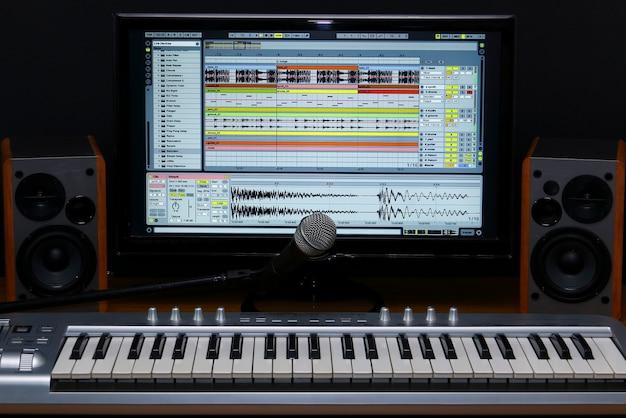 Home recording studio. screen keyboard, speakers and microphone.