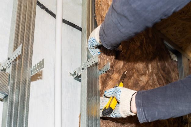 집 수리 작업자가 석고보드 클래딩 열을 추가하기 위해 벽에 미네랄 울을 부착합니다.