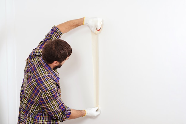 家の改修サービス。塗装前にマスキングテープを使用して画家。仕事で画家の男。