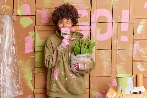 家の修理と変身のコンセプト。スウェットシャツの縮れ毛の女性がペイントブラシで口を覆うアパートで修理を行う