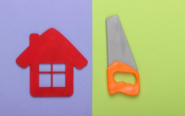 家の修理の概念または家の建設。紫緑色の背景に家の置物とおもちゃのミニのこぎり。上面図