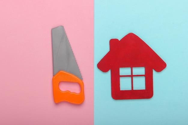 家の修理の概念または家の建設。ピンクブルーの背景に家の置物とおもちゃのミニのこぎり。上面図