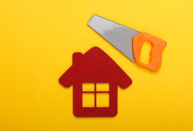 家の修理の概念または家の建設。黄色の背景に家の置物とおもちゃのミニのこぎり。上面図