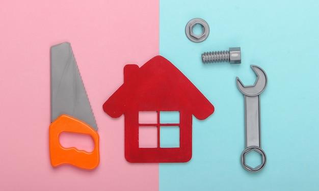 家の修理の概念または家の建設。ピンクブルーのパステルカラーの背景に家の置物、おもちゃの作業ツール。上面図