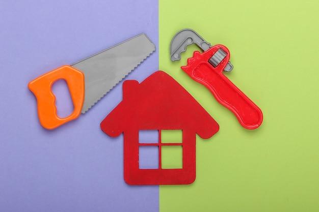 家の修理の概念または家の建設。家の置物、紫緑色の背景のおもちゃの作業ツール。上面図