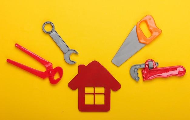 家の修理の概念、または家の建設。家の置物、黄色の背景におもちゃの作業ツール。上面図