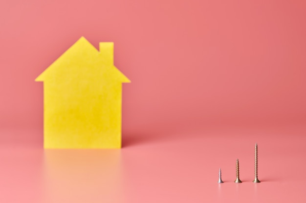 Home repair and redecorated concept. house renovation. screws and yellow house shaped figure on pink background.