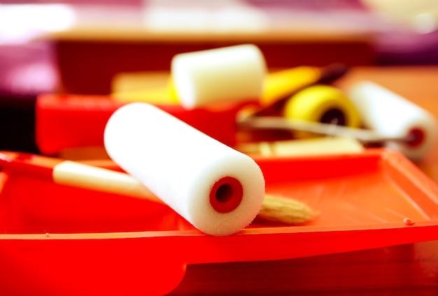 家の修理ツール。プラスチック容器の壁の着色のためのフォームローラーをクローズアップ。