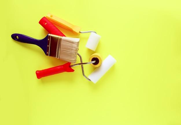 Инструменты для ремонта дома на ярко-желтом фоне. пенные валики и синтетические кисти для окраски стен.