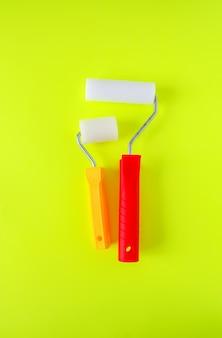 Инструменты для ремонта дома на ярко-желтом фоне. два ролика пены для окраски стен крупным планом.