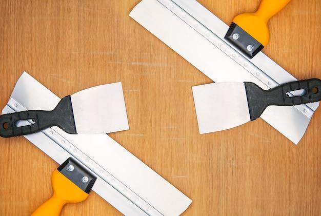 Инструменты для ремонта дома. шпатели на деревянных фоне.