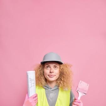집 수리공은 아파트 방 장식으로 바쁜 그림 붓과 종이 청사진 위에 집중된 곱슬머리를 가지고 있으며 헬멧 유니폼 포즈를 취합니다.