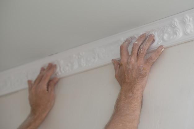 집 수리. 바게트를 천장에 고정하는 작업자의 손 클로즈업.
