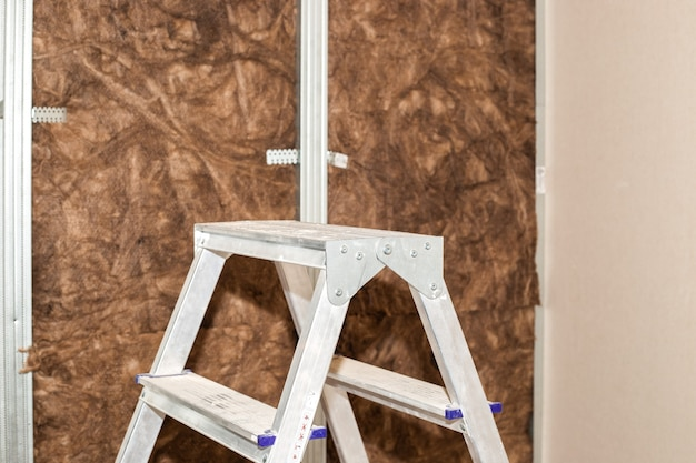 Home repairs a folding ladder stands against the background of a wall lined with mineral wool for
