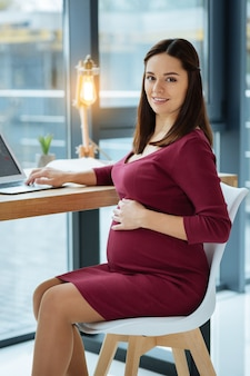 Home rest. young pregnant woman expressing delight while sitting at the table and using a laptop