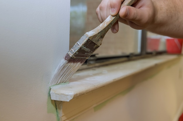 Home restoration worker painting using paint brush a window frame trim