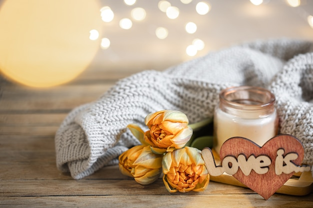 Домашний романтический натюрморт love на день святого валентина с цветами и элементами декора на размытом фоне с боке.