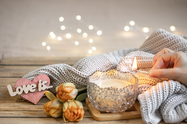 Home romantic still life with burning candle, decor, fresh flowers and knitted element on blurred background with bokeh.