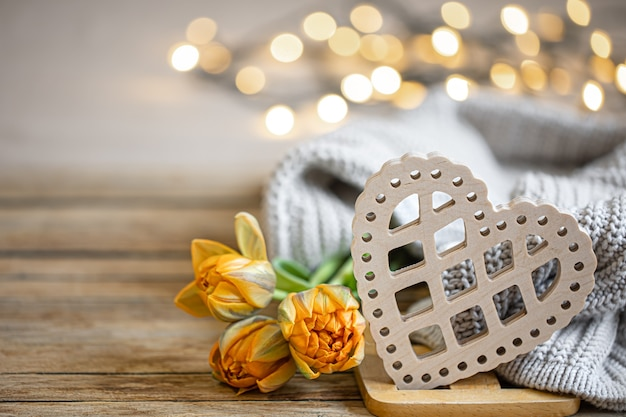 Home romantic still life with wooden decorative heart and knitted element on blurred background with bokeh copy space.