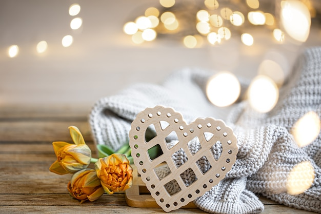 Home romantic still life with wooden decorative heart and knitted element on blurred background with bokeh.