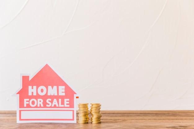 Icona di casa in vendita con monete impilate sullo scrittorio di legno