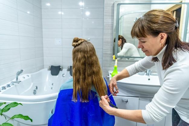 検疫中のホームサロンの散髪。成熟した女性はバスルームで若い女の子に長い髪をカットします。母は美容師で、パンデミックのために娘の髪を切っています。家の娯楽、余暇。