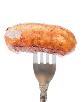 Home sausage fried in oil on a fork.