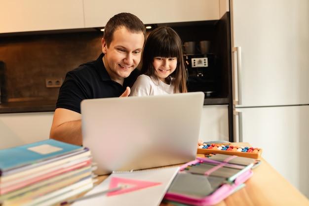 自宅学習。オンライン学習。女の子と彼女の父親の自宅、オンラインレッスン、ラップトップでのビデオ通話。遠隔教育。家族の一体感
