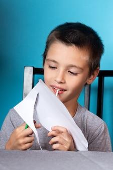 ホームスクーリング。少年は宿題をします、紙を切ります