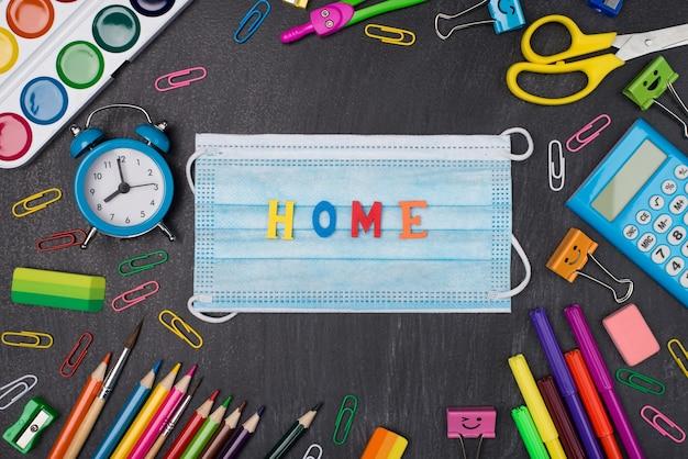Концепция домашнего обучения. фотография красочных канцелярских принадлежностей с маской и домашним словом в центре на доске сверху вверху сверху