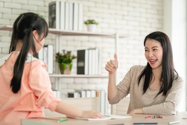 바이러스 대유행 동안 가정에서 학습하는 홈 스쿨링. 바이러스로부터 보호하기 위해 외과용 안면 마스크를 쓰고 거실에 딸과 함께 있는 아시아 여성. 프리미엄 사진