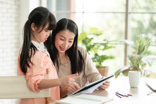 바이러스 대유행 동안 가정에서 학습하는 홈 스쿨링. 바이러스로부터 보호하기 위해 외과용 안면 마스크를 쓰고 거실에 딸과 함께 있는 아시아 여성.