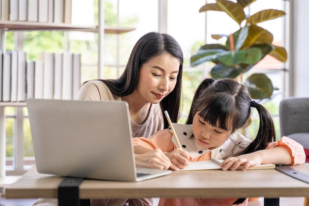 바이러스 대유행 동안 가정에서 학습하는 홈 스쿨링. 거실에 딸과 함께 있는 아시아 여성, 바이러스로부터 보호하기 위해 외과용 안면 마스크를 쓰고 있습니다.