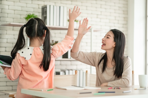 ウイルスパンデミック時の自宅でのホームスクーリング学習。リビングルームで娘と一緒にアジアの女性。ウイルスから保護するためにサージカルマスクを着用しています。