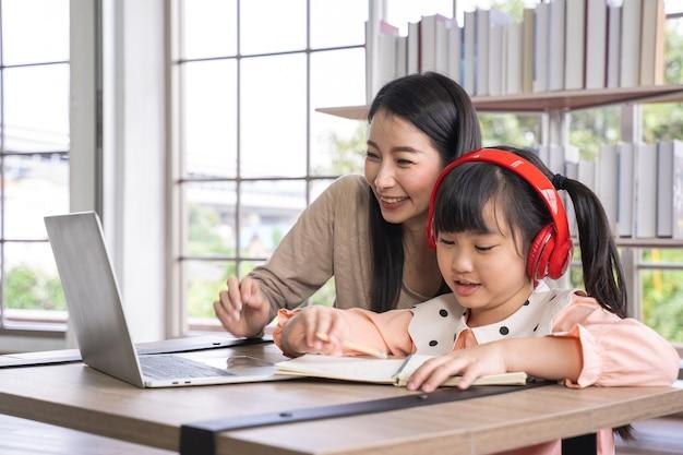 그녀의 딸과 함께 바이러스 전염병 아시아 여성 동안 집에서 학습 홈 스쿨링