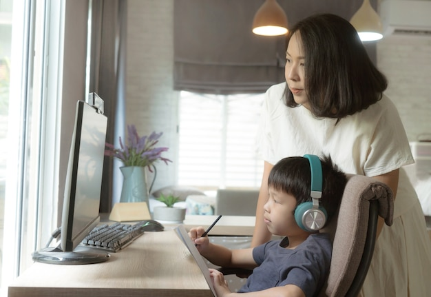 Home schooling mom helps the child learn on online education on computer at home
