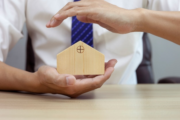 Home security concept insurance for real estate protecting gesture of man and house model