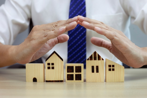 Home security concept insurance for real estate protecting gesture of man and house