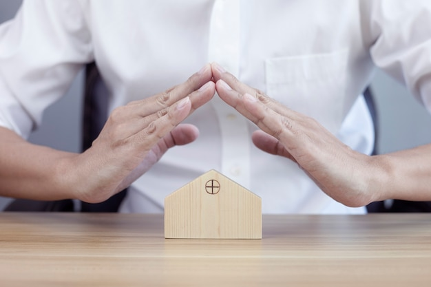 Home security concept protecting gesture of man and house model