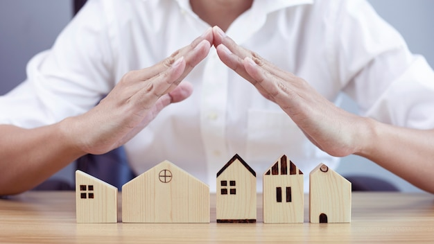 Home security concept and protecting gesture of man and house model