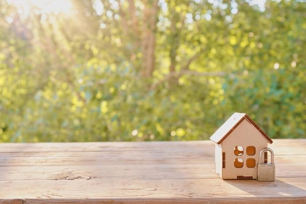 Концепция домашней безопасности: деревянный модельный дом и замок на деревянной поверхности. безопасность дома